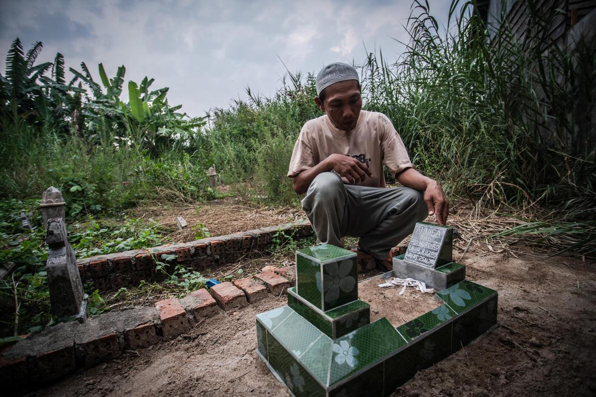 蘇門答臘居民 Abi 待在女兒的墓旁,他兩個月大的女兒死於霧霾導致的呼吸困難。