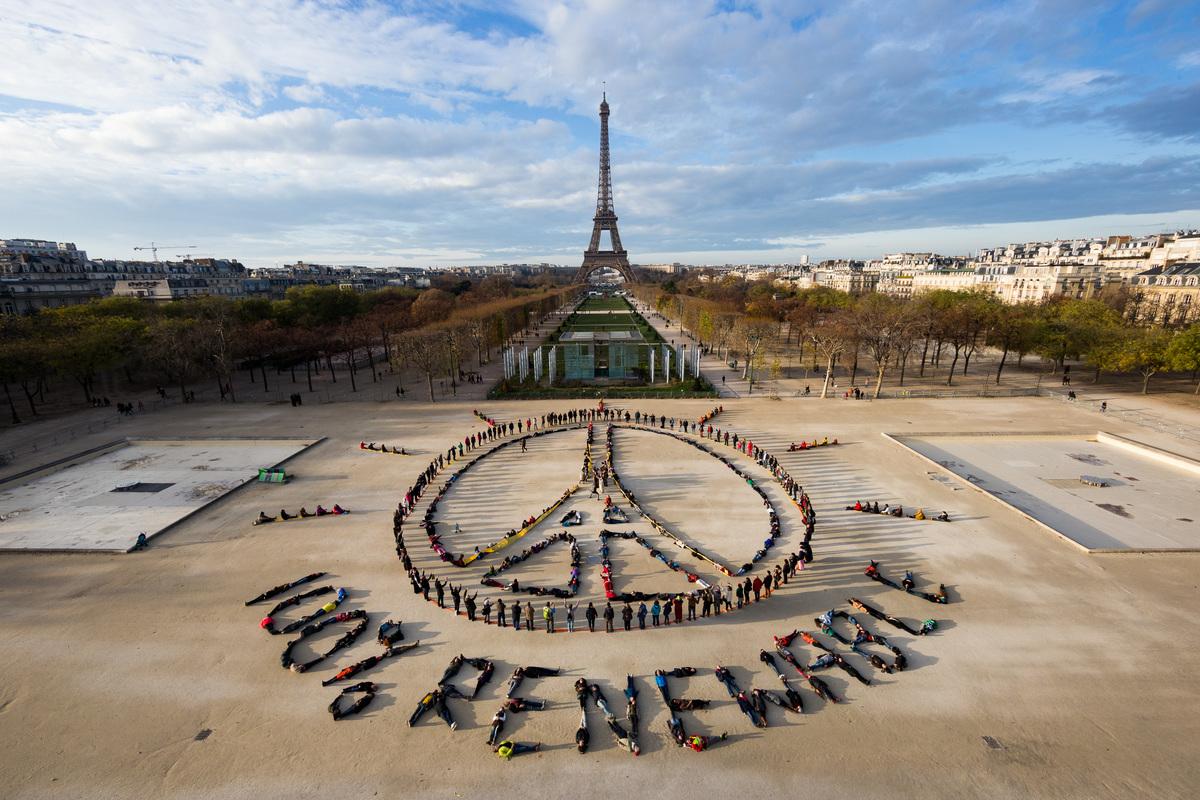 2015年聯合國氣候峰會前夕,綠色和平法國行動者於巴黎鐵塔前廣場,以數百人排出和平與「100%再生能源」字形,倡議全球加速能源轉型。