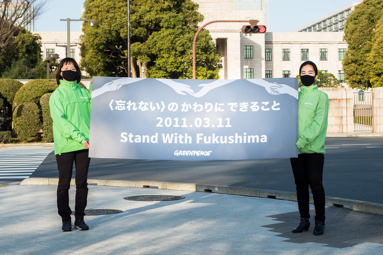 2021年3月11日,綠色和平東京辦公室在國會大廈前,手舉「與福島同行」標語,呼籲日本政府轉向再生能源的未來。