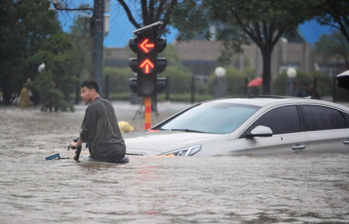 2021年7月中國鄭州遭遇暴雨,民眾在馬路上推著單車,水面高至腰間,汽車也寸步難行。© visual.people