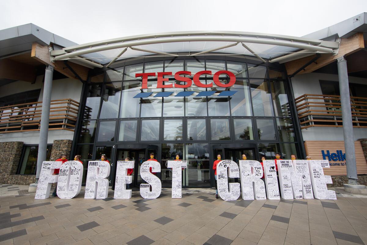 綠色和平行動者在英國零售業巨擘Tesco的總部前放置了「森林犯罪」標語,迎接前來參加Tesco年度股東大會的代表們。這座1.5公尺高的裝置上有上千名公眾的連署與留言,要求該企業停止販賣涉及毀林行為的商品。© Suzanne Plunkett / Greenpeace