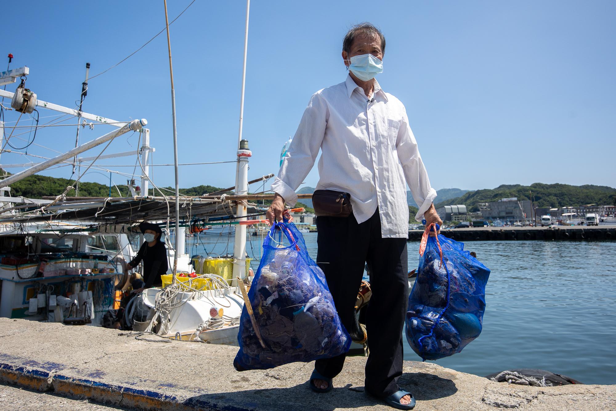 林新永船長拿著海洋垃圾,此次淨海是由他號召25漁船,共35位漁民共襄盛舉。