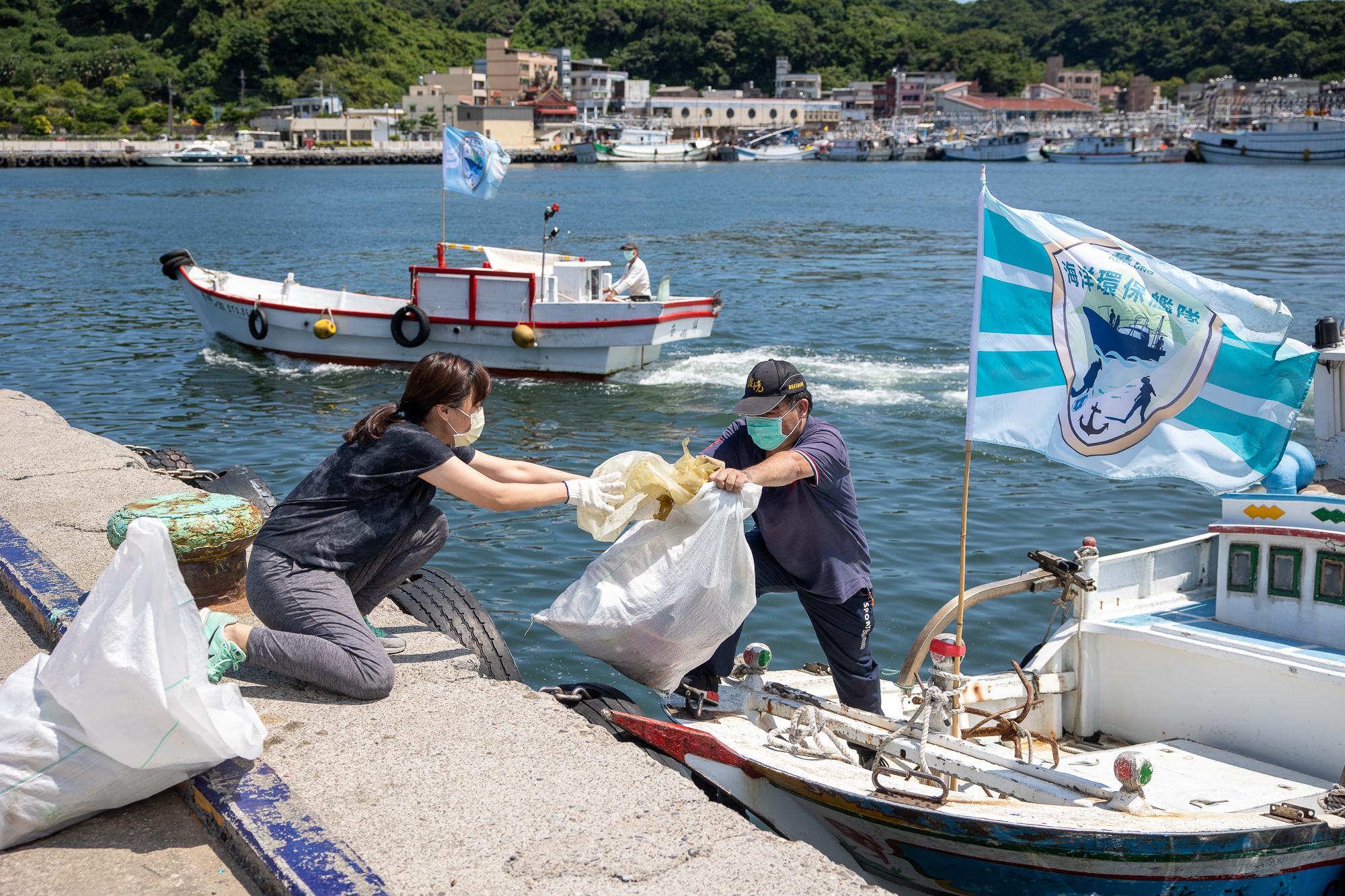 綠色和平志工從船長手中接過垃圾,做後續分類、統計和處理。