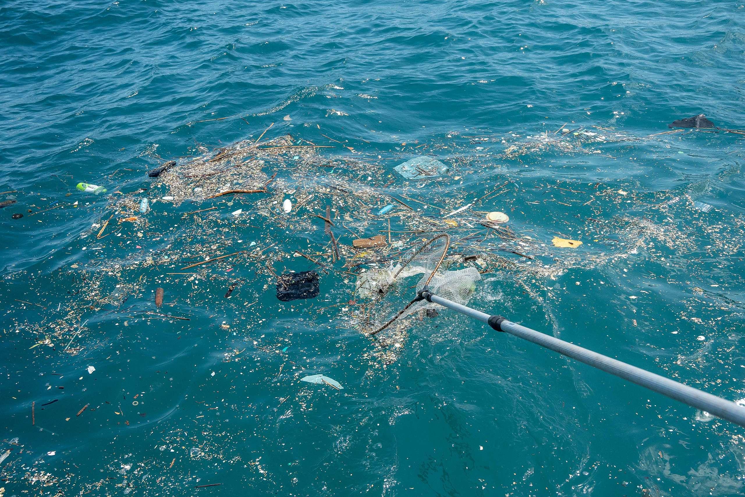 漁民除了載送潛水志工清除的海底廢棄物,也在船上撈起海面上漂浮的垃圾。