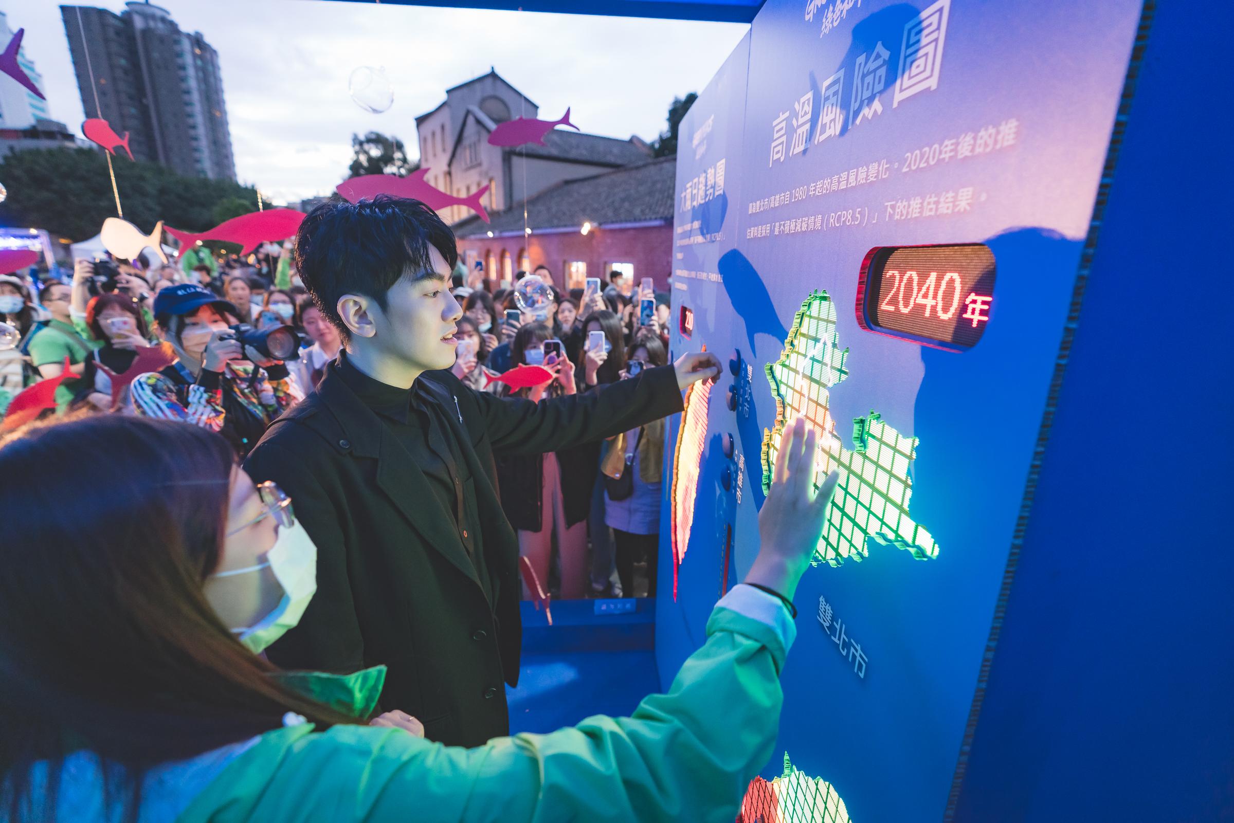 李友廷在現場表演後,體驗綠色和平設置的未來體驗屋,對大雨日趨勢圖及高溫風險圖表示印象深刻。
