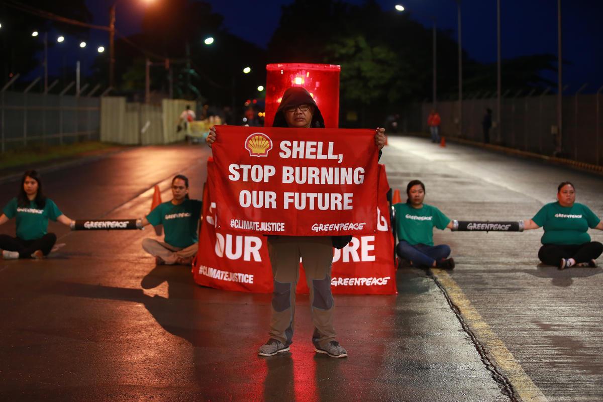 2019年,綠色和平菲律賓行動者於殼牌石油公司在馬尼拉南部的煉油廠入口,舉牌倡議「停止燃燒我們的未來」,要求企業為氣候危機負起責任。