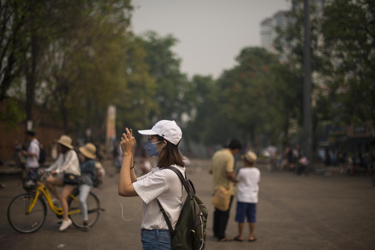 ประชาชนสวมหน้ากากป้องกันฝุ่นพิษ PM 2.5 บริเวณประตูท่าแพในวันที่ค่าดัชนีคุณภาพอากาศ PM 2.5 อยู่ในระดับมากกว่า 300 ซึ่งมีอันตรายต่อสุขภาพ. © Vincenzo Floramo / Greenpeace