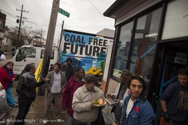 Volunteers distribute donated food and supplies at a makeshift base to help residents of Queens still without power after Hurricane Sandy. The Greenpeace solar truck Rolling Sunlight supplied power to charge cell phones.
