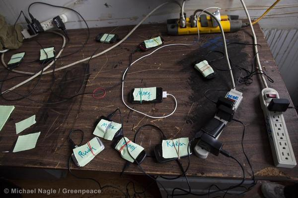 Cell phones charge at a makeshift base to help residents of Far Rockaway in Queens still without power after Hurricane Sandy. The Greenpeace solar truck Rolling Sunlight supplied power.