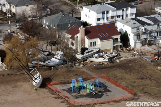 A cleaned up playground in the foreground is ready for children while boats are still piled up against houses in this Staten Island neighborhood