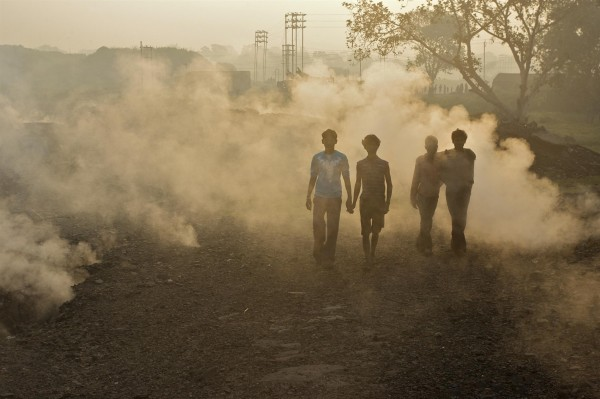 Local people in Aina village and toxic fumes rising from the ground caused by burning coal at the nearby Jharia coal mine.