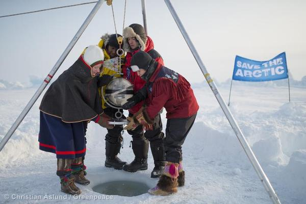 Team Aurora lowers a titantium time capsule with the names of 2.7 million people who want to save the Arctic from the impacts of climate change and pollution of oil production.