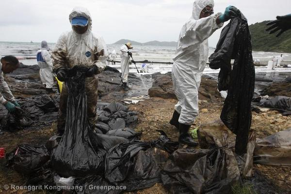 Rescue workers, local volunteers and PTT personnel attempt to clean up the oil spill at Ao Phrao beach in Ko Samed, Rayong Province.