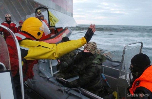 A Russian Coast guard officer is seen pointing a knife at a Greenpeace International activist