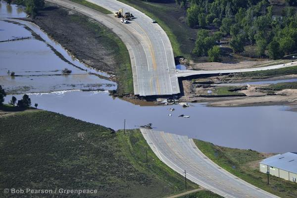 Waters recede around a washed out bridge on Colorado Highway