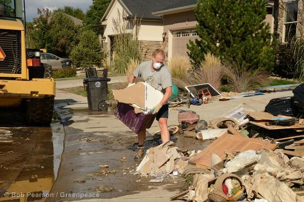 A man carries a load of ruined drywall as residents clear their houses of debris