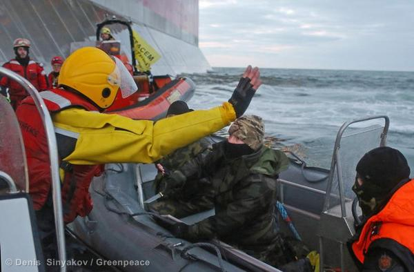 A Greenpeace activist raises his arms in surrender as a Russian coast guard threatens with a knife