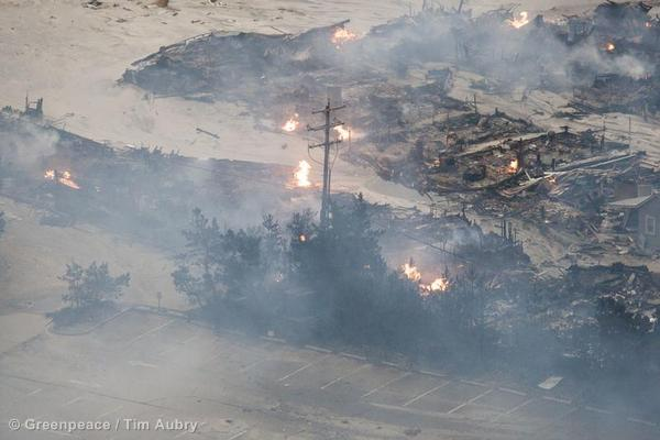 An aerial view of a burnt out neighborhood with open natural gas fires from pipes that broke in damaged buildings during Hurricane Sandy.