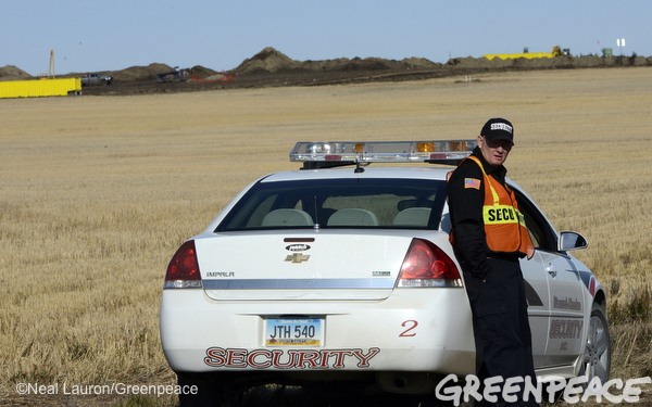 A private security worker is stationed near workers with heavy equipment are mounding soil around the perimeter of huge oil spill outside of Tioga, North Dakota