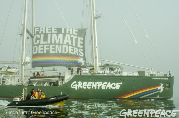 The Rainbow Warrior, Greenpeace's iconic flagship, sails alongside an inflatable as she arrives in San Francisco