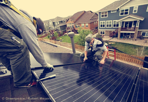 Namaste solar installers Josh Ford and Jed Brunk on a rooftop in Aurora during a photo voltaic system installation.