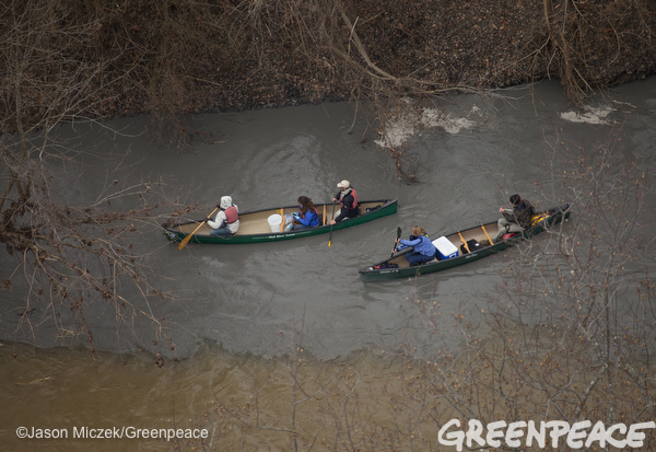 People in canoes maneuver in the Dan River where a coal ash spill changes the color of the river in Eden, North Carolina on February 4, 2014. It was the 3rd biggest coal ash spill in American history.