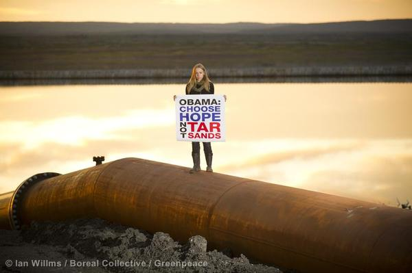 A greenpeace activist stands in front tar sands tailings in Alberta.