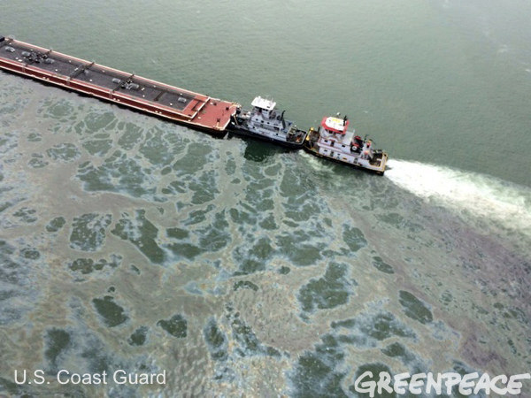 A tug pulling the partially submerged oil barge.