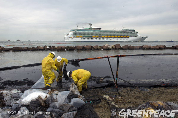 Clean-up crews fill bags with oil-absorbent material in Galveston, Texas, March 26, 2014, as a cruise ship goes by in the background.  Photo coutesy US Coast Guard; photo by Petty Officer 2nd Stephen Lehmann.