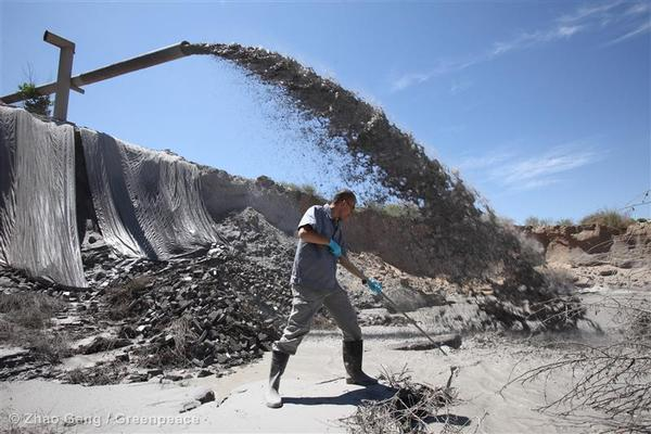 A Greenpeace activist in a coal ash disposal site that belongs to the Yuanbaoshan Power Plant, in Chifeng, Inner Mongolia. Less than half a kilometer away, there is a dairy collection station for a famous dairy company.