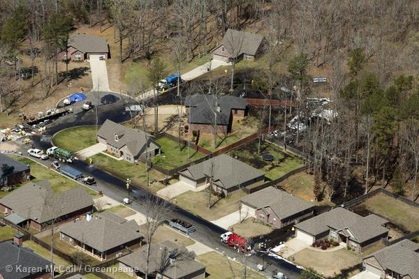 Workers surround houses in Mayflower, Arkansas, in an attempt to clean up an oil spill from Exxon's Pegasus pipeline. A leak was discovered in the subdivision forcing the evacuation of 22 homes.