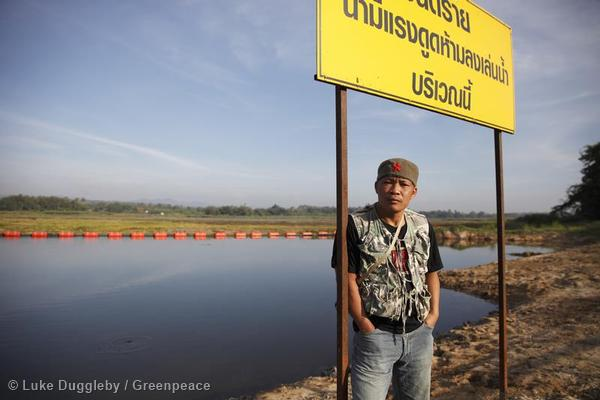 A man stands in front of a reservoir where the Mae Moh power plant had released large quantities of waste water continuously.
