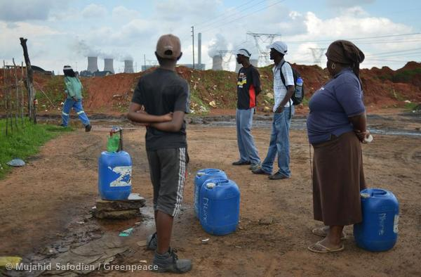 South Africa, MNS informal settlement. Community members wait to fill up water containers at a community tap next to the coal washing station. The water is approximately 500 meters from the settlement.