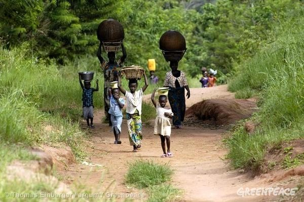 Local women and children on a road coming from a water hole, in the DRC.