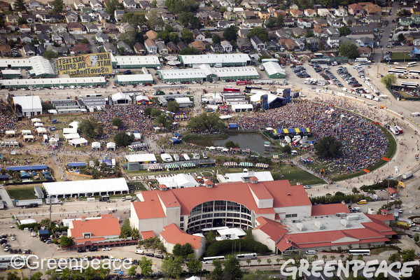 A plane flies a Greenpeace banner that says 'Love JazzFest/Hate Oil Spills' over the crowd at JazzFest.