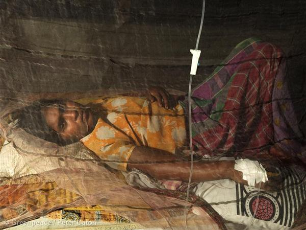 A young women lies behind a net on a makeshift bed at a medical camp in Bali island in the Sundarbans. Reports of cholera are increasing due to stagnated water which is also giving birth to an influx of mosquitoes. Scientists estimate that over 70,000 people, living effectively on the front line of climate change, will be displaced from the Sundarbans due to sea level rise by the year 2030.
