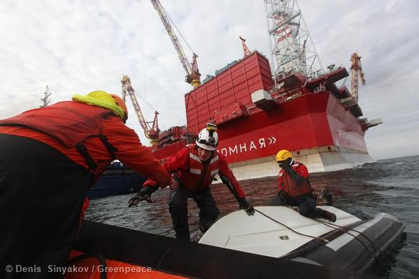 Two activists are helped out by other crew members after they attached their inflatable to the mooring lines linking the Anna Akhmatova (a Gazprom passenger vessel) and the Prirazlomnaya oil platform.