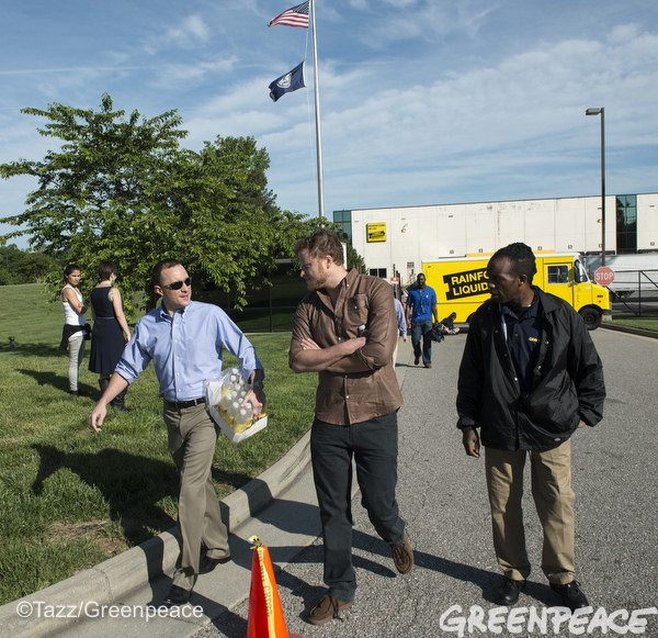 A Lumber Liquidator employee talks with Greenpeace campaigner Daniel Brindis and a Greenpeace activist outside company headquarters.