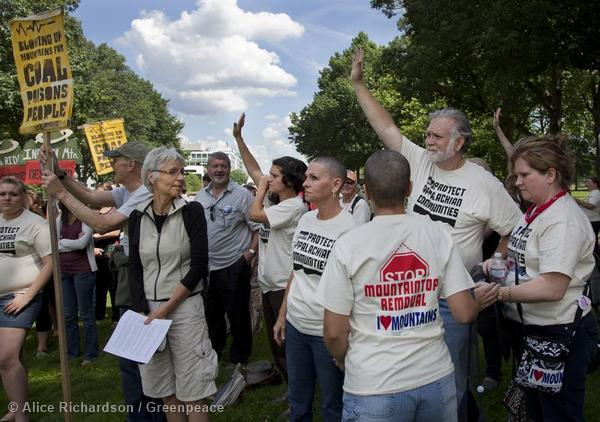 Activists raise their hands to volunteer to shave their heads to show solidarity with the families affected by mountaintop removal coal mining in Appalachia.