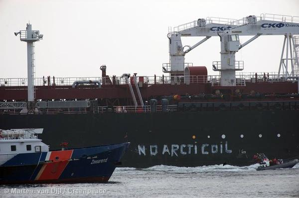 Greenpeace activists aboard inflatables paint No Arctic Oil on the side of an oil tanker carrying the first shipment of oil extracted from Arctic waters.