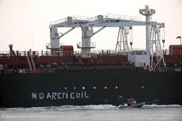 Greenpeace activists aboard inflatables paint No Arctic Oil on the side of the Mikhail Ulyanov oil tanker.