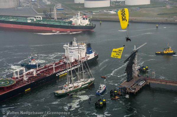 The Greenpeace ship Rainbow Warrior, para-gliders, and Greenpeace inflatables protest against the first shipment of Russian arctic oil in the harbor of Rotterdam.