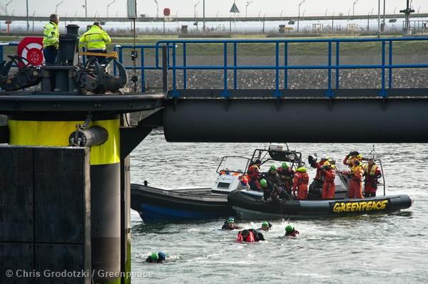 Greenpeace swimmers, the Greenpeace ship Rainbow Warrior and Greenpeace inflatables protest against first shipment of arctic oil in the harbour of Rotterdam.