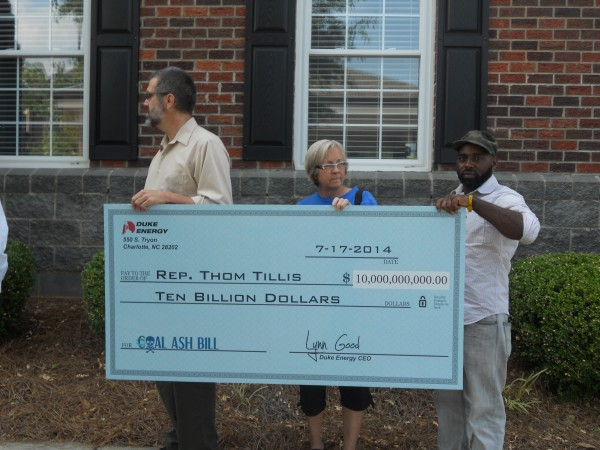 Charlotte activists deliver a mock check from Duke Energy to NC Speaker of the House Thom Tillis, who was key in pushing through the weak coal ash bill.