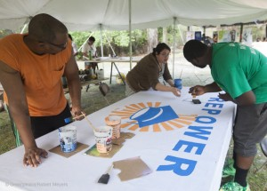 Volunteer paint a Repower Our Schools Banner