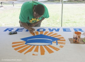 A Volunteer Paints a Banner for Repower Our Schools