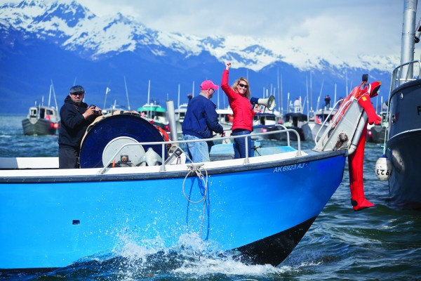 Protest organizer Emily Stolarcyk of the Eyak Preservation Council celebrates the good turnout in her efforts to object to the Navy's plans to conduct war games in the Gulf of Alaska. Driving his fishing boat is James Mykland on the Exodus and Lloyd Montgomery (left).