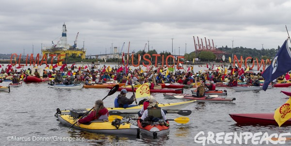 Activists participate in the sHell No Flotilla part of the Paddle In Seattle protest.  Nearly a thousand people from country gathered May 16, 2015 in Seattle's Elliott Bay for a family-friendly festival and on-land rally to protest against Shell's Arctic drilling plans.  Photo by Greenpeace