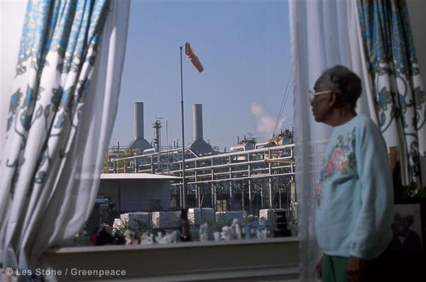 Clara Smith, 96, stands at the window of her home looking out at a Shell oil refinery just a couple of yards away.