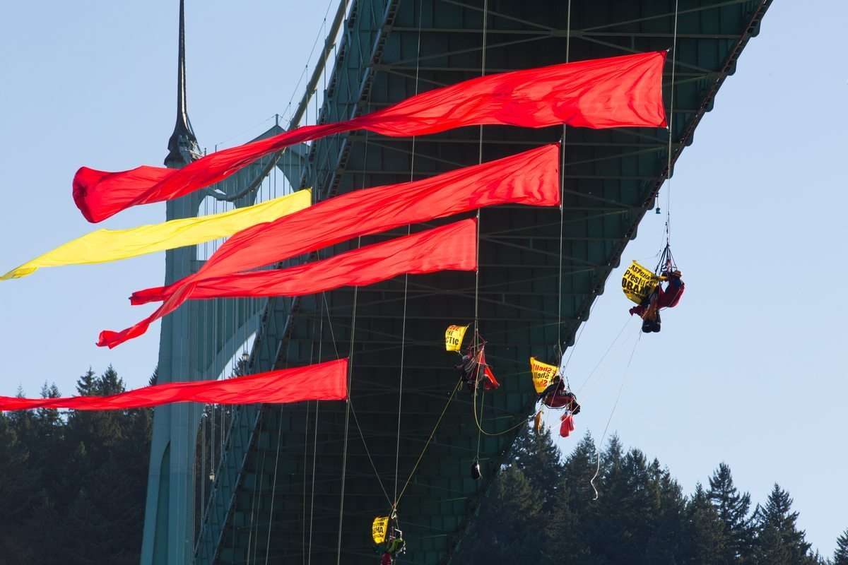 Colorful streamers float on the wind under the St. Johns Bridge where climbers and kayaktivists attempt to prevent the Shell-leased icebreaker MSV Fennica from joining Shell's Arctic oil drilling fleet. The Fennica came to Portland to have a gash in its hull repaired after being damaged in the Arctic as Shell prepared to explore for oil in the Chukchi Sea.